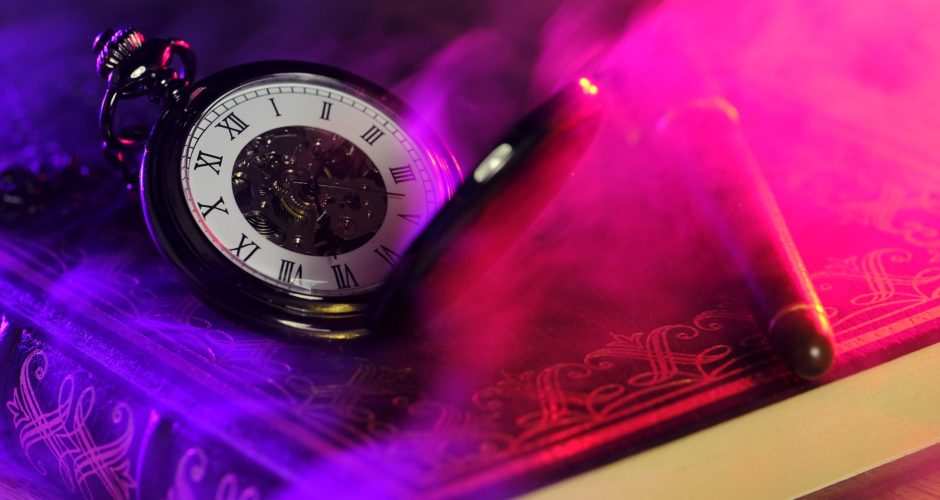 pocket watch on a book with magic smoke obscuring a pen